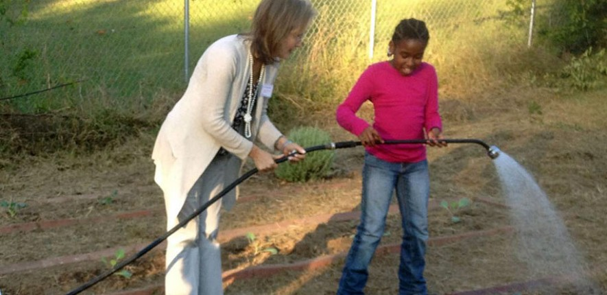 Kathy Knight assists a student working in a school garden.