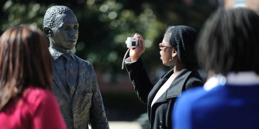 Visitors take photographs at the James Meredith statue.