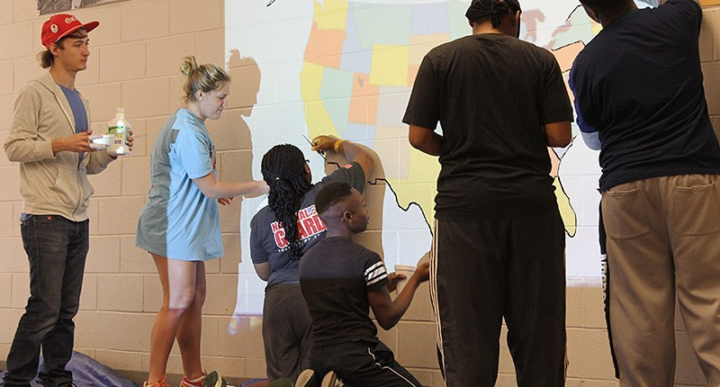 During an alternative spring break, student volunteers paint maps at West Tallahatchie High School.